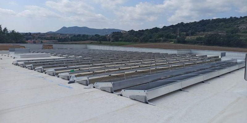 Instalación de paneles solares en cubierta industrial con estructuras metálicas